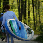 Woman Carrying Earth River SUP 9-6 SKYLAKE GREEN