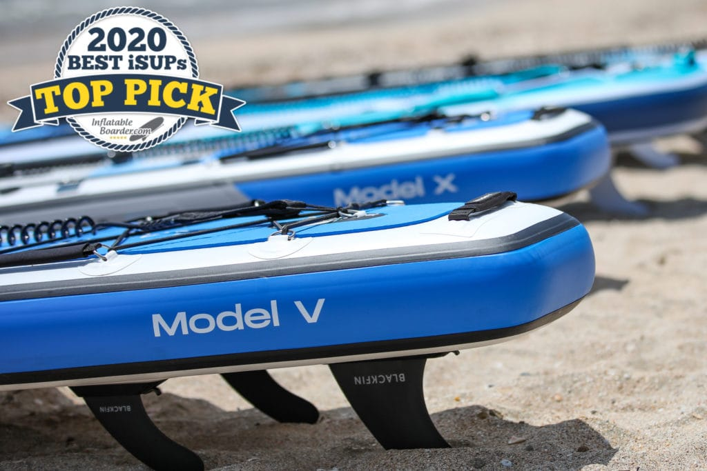 """BLACKFIN Model V SUP on beach with other boards. Includes a badge that reads """"2020 Best iSUPS TOP PICK"""""""