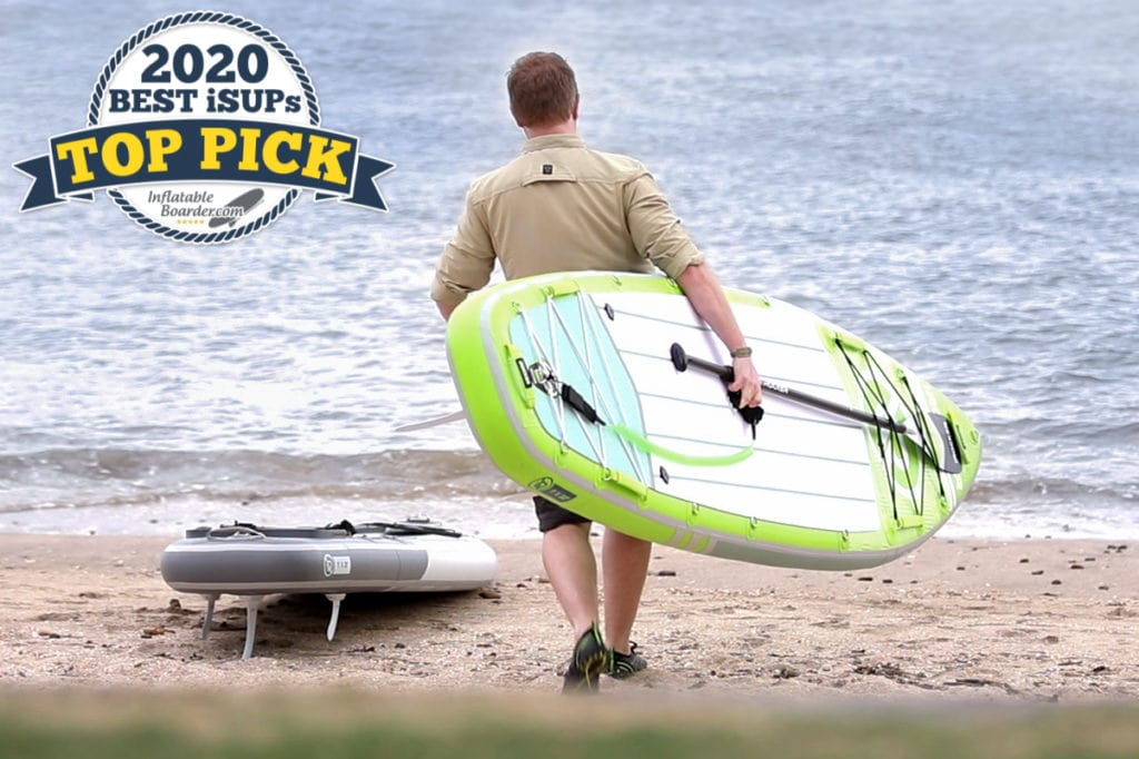 """Man on beach carrying iROCKER All-Around 11 - Includes badge that reads """"2020 Top Pick SUP"""""""
