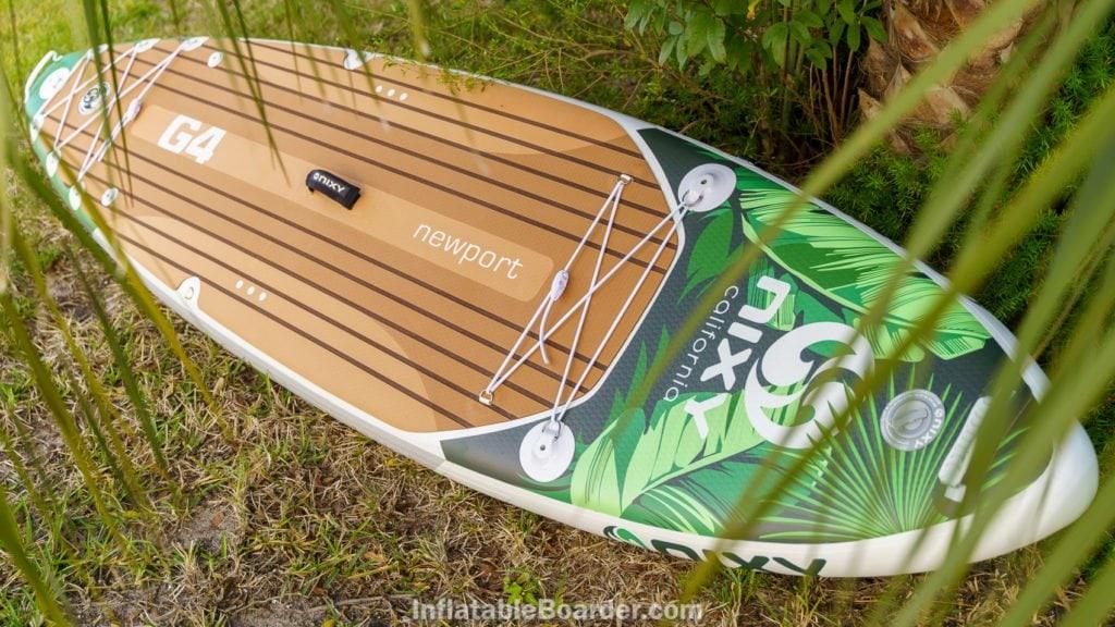 Green NIXY Newport sup behind palms.