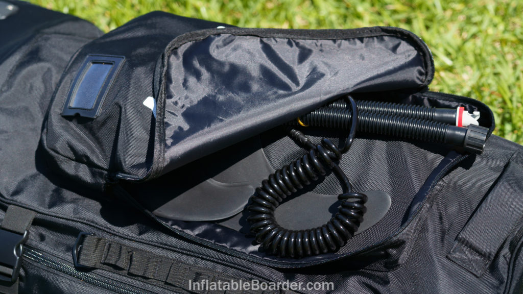 The top of the bag features a large accessory pocket and luggage tag.