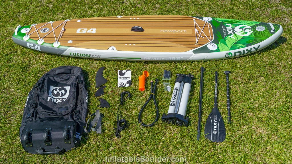 Palm-colored NIXY Newport G4 with accessories, including bag, 3 fins, pump, paddle, leash, repair kit, manual, and compression strap.