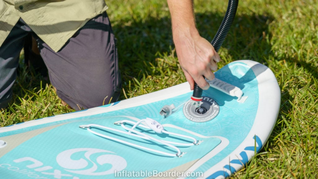 Attaching the pump hose to the inflation valve at the front of the board