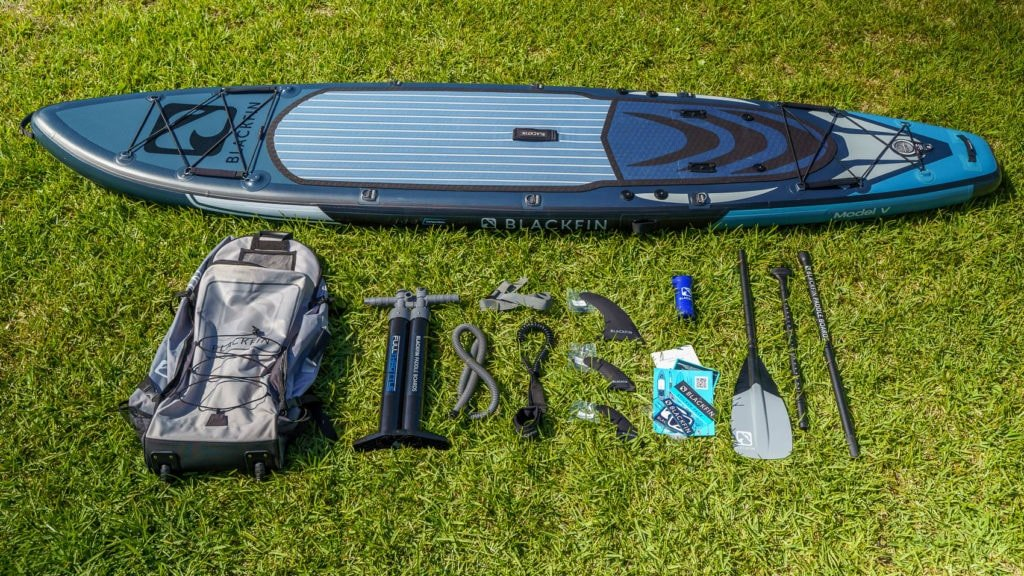 Overview of the Model V's accessory bundle: includes color-matched bag, pump, SUP leash, color-matched paddle, 3 fins, repair kit, compression strap, manual, warranty card, and sticker pack.