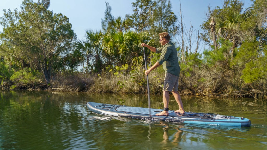 Side view of paddling the board on a calm tropical river.