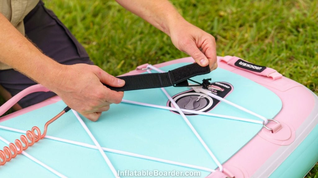 The coiled SUP leash is easily attached via velcro strips.