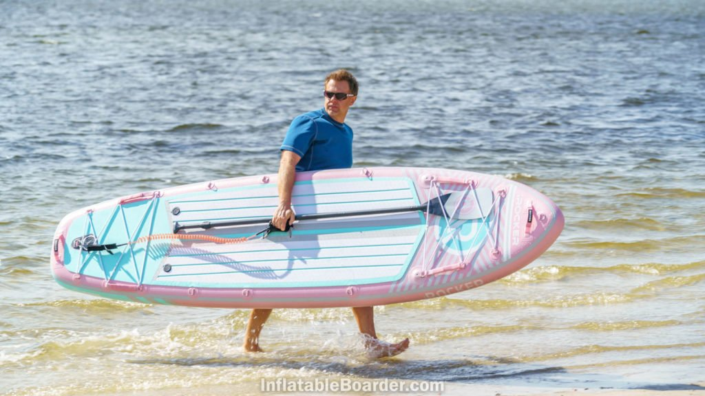 A man carrying the pink board out of the ocean.