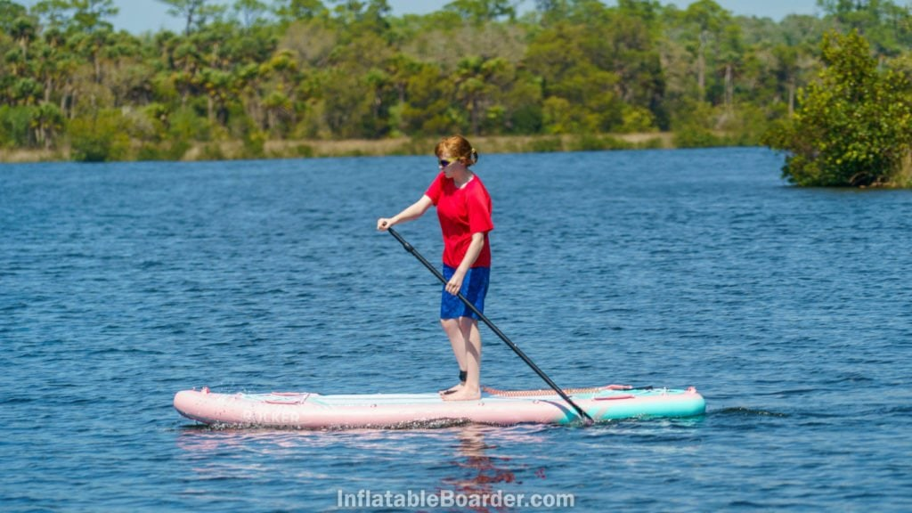 Side shot of a teen woman paddling the board on calm water.