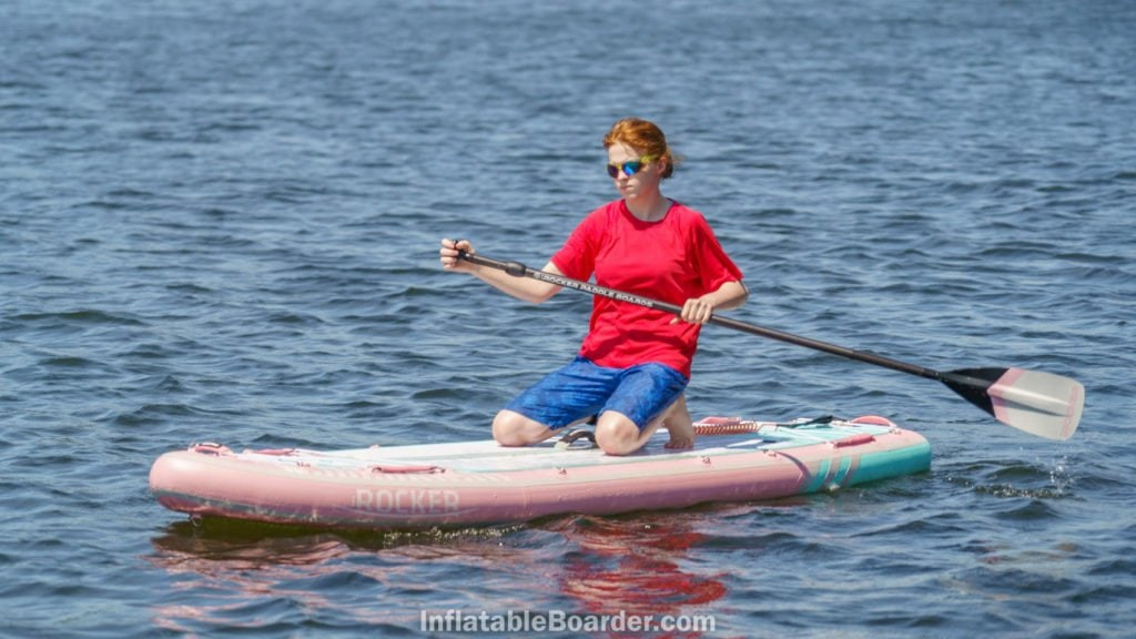 A teen kneeling on the board to paddle for extra stability.