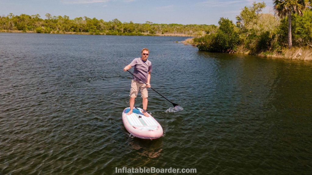 A man paddling the board on a river.