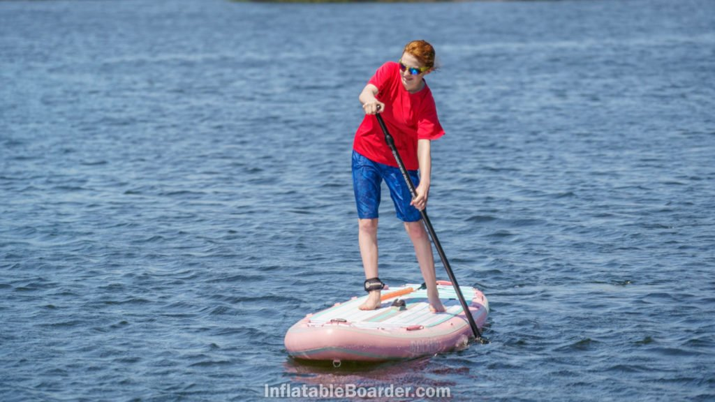 A teen paddling the SUP on open water.