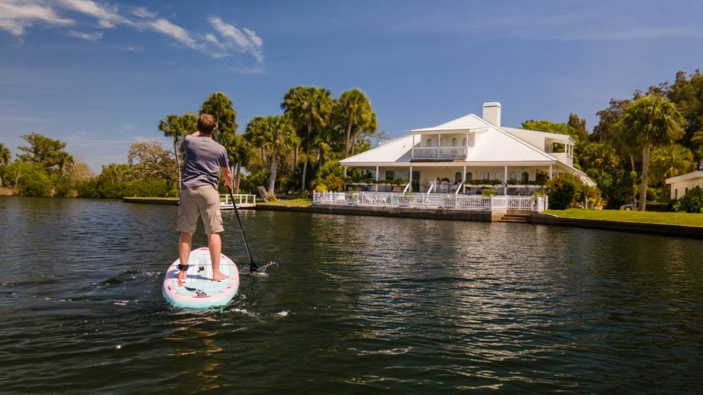 A man paddling the All-Around 10' towards a resort.