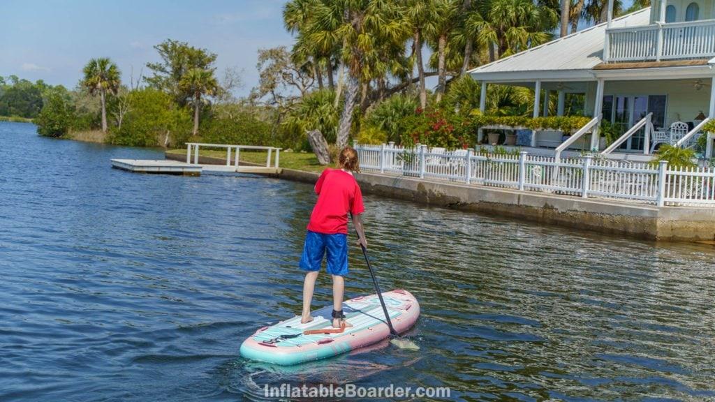 A teen paddling the pink board towards shore.