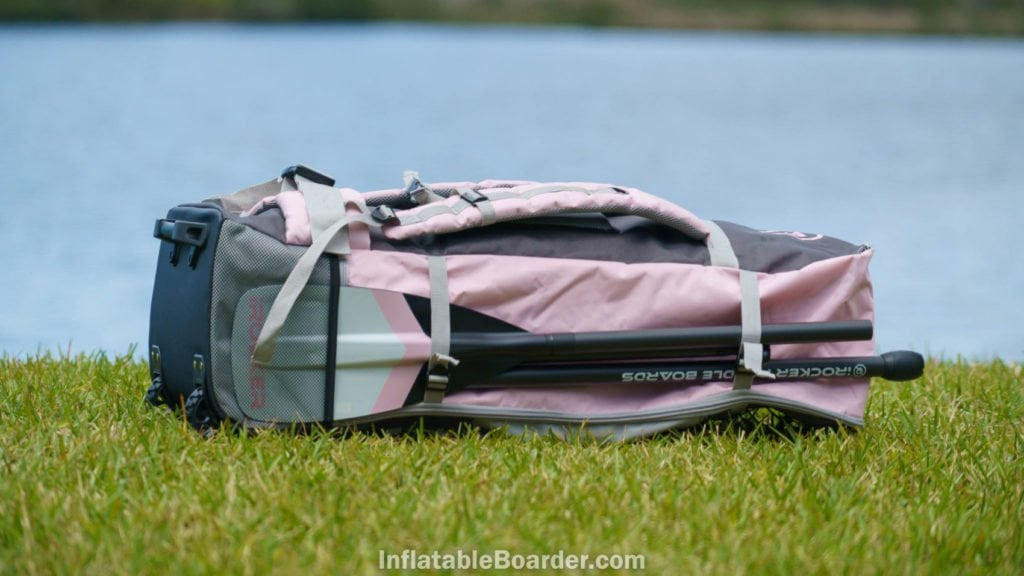 Side of the pink bag with paddle pocket and two straps.