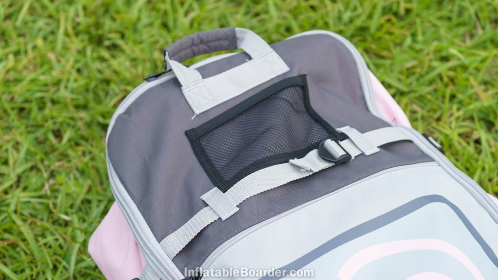 Top of the bag with handle, small mesh pocket, and compression strap.