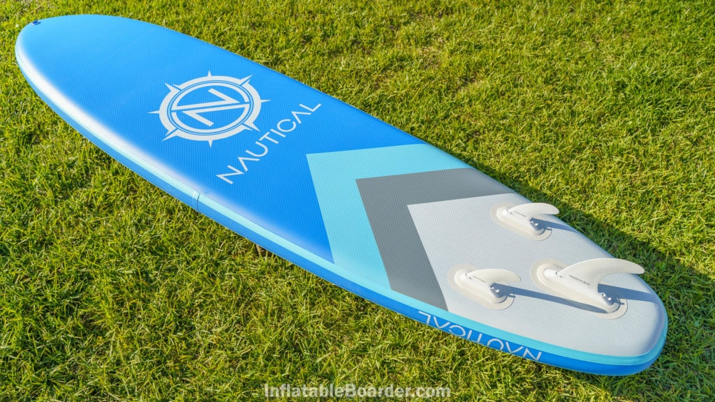 """Overview of the bottom fo the 2021 NAUTICAL 10'6"""" paddle board, featuring three quick-attach fins and large logo."""