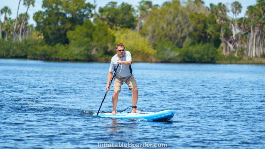 Paddling the board on a calm bay.