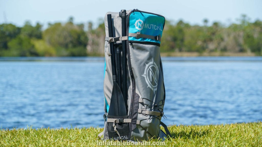 The Nautical bag with paddle, standing up near a lake.