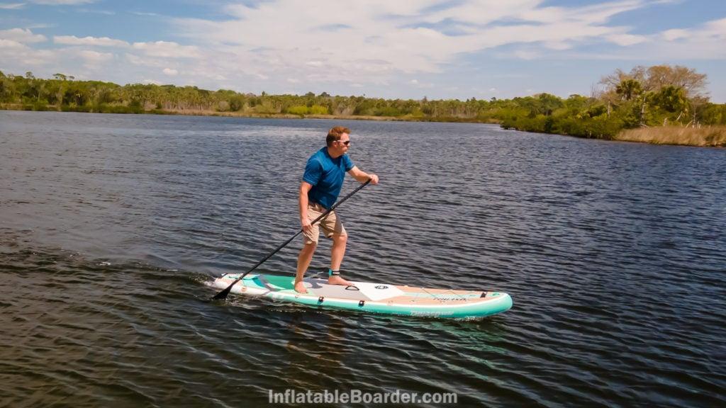 A man paddling fast on a lake.