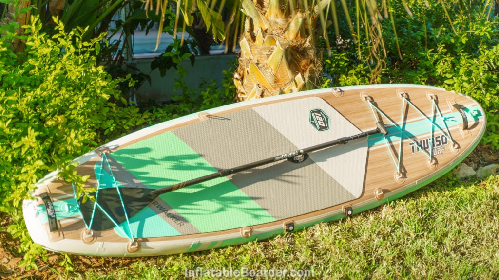 The Waterwalker 120 inflatable paddle board beneath palms at sunset.