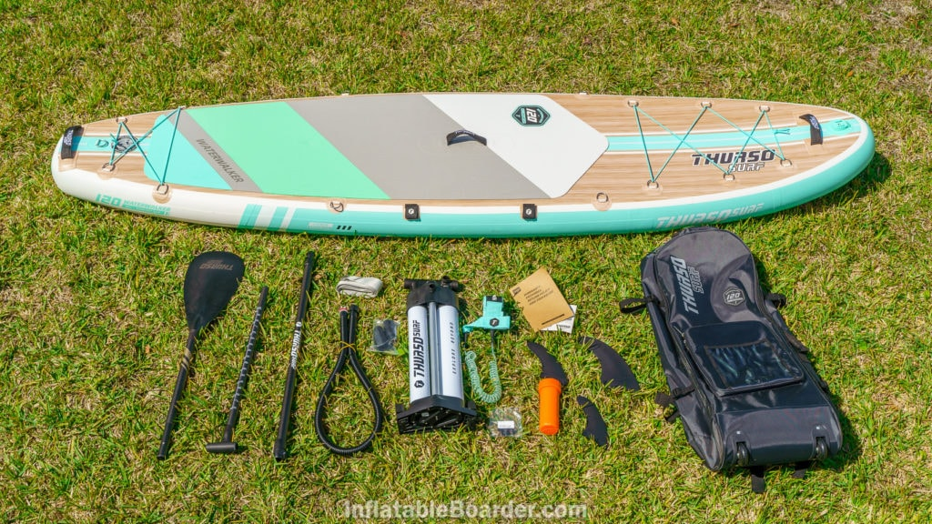 Aqua-colored Thurso Waterwalker 120 with accessories, including bag, 3 fins, pump, paddle, leash, repair kit, manual, and compression strap.