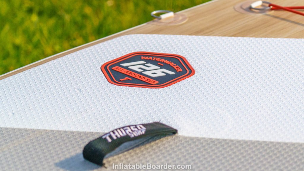 """Color matched rubber badge at the center of the board reads """"Waterwalker 126 All-Around SUP""""."""