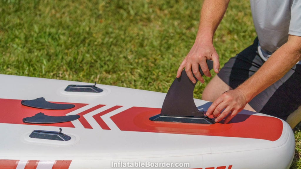 Attaching the three quick-connect fins on the bottom of the board.