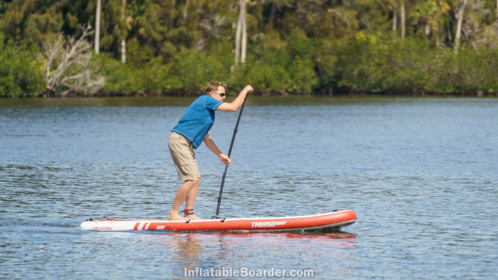 Side shot of paddling the board hard for speed.