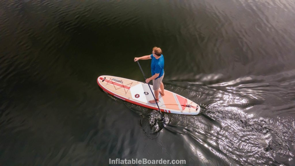 Paddling the crimson board from above on smooth water.