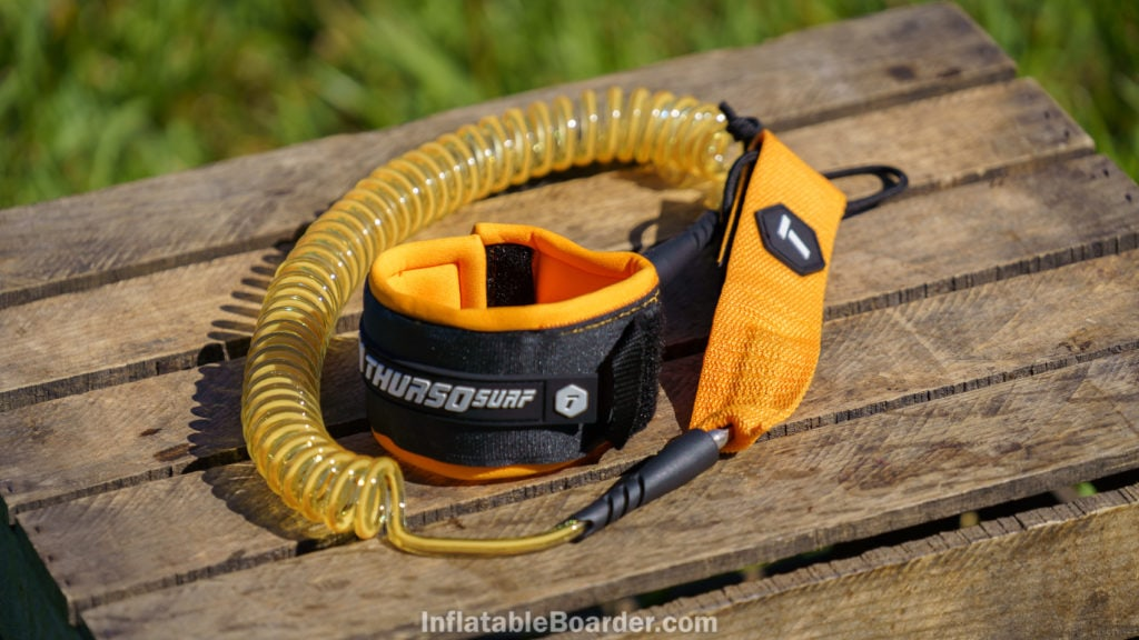 The coiled SUP leash is color matched to the board's theme.