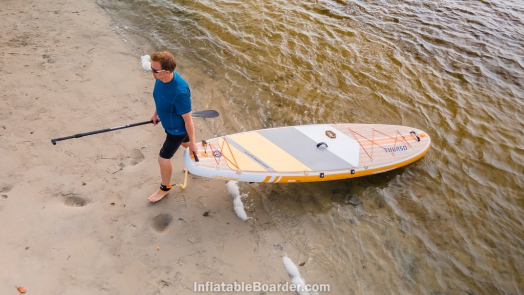Carrying the board out of the ocean to a beach, viewed from above.