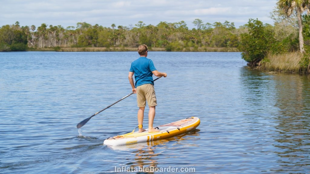 Paddling the board on calm water towards shore.