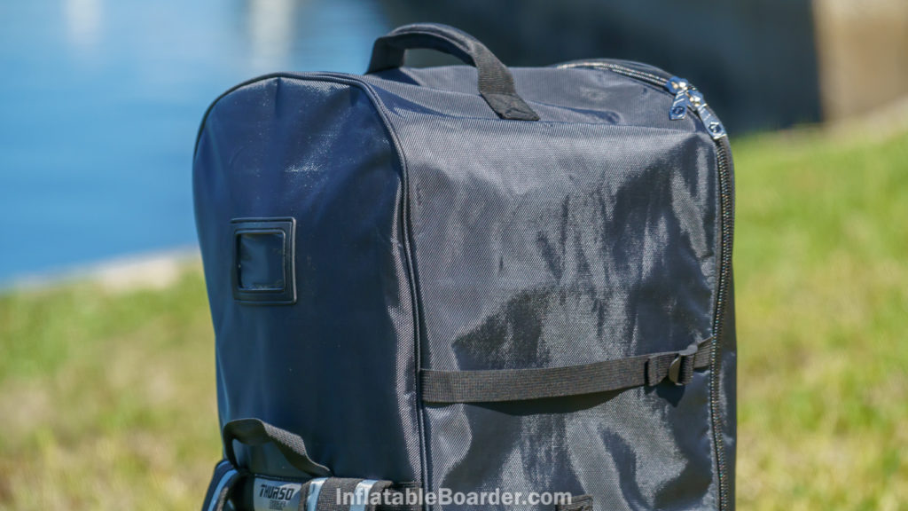 The top of the bag has a padded handle, compression straps, and luggage tag.