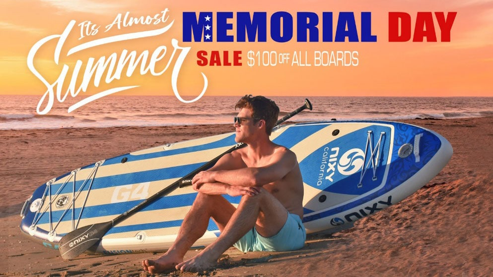 Man on beach with NIXY G4 board. Text reads: Memorial Day Sale - $100 off all boards