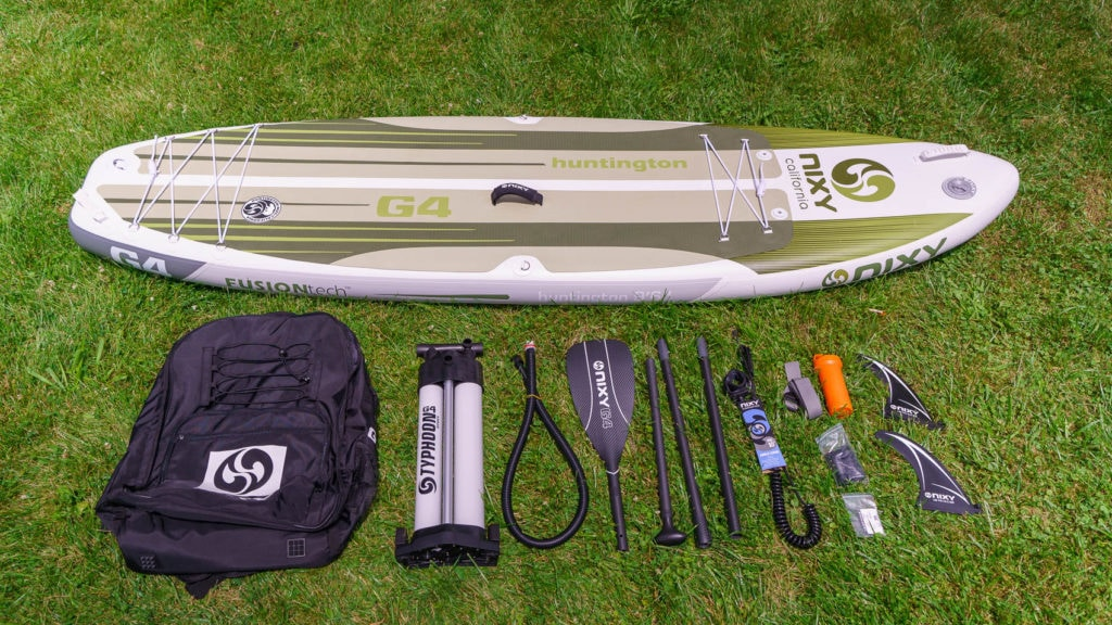 Unboxed NIXY Huntington G4 with accessories, including compact bag, dual chamber pump, 4-piece paddle, coiled SUP leash, compression strap, repair kit, and 2 fins.