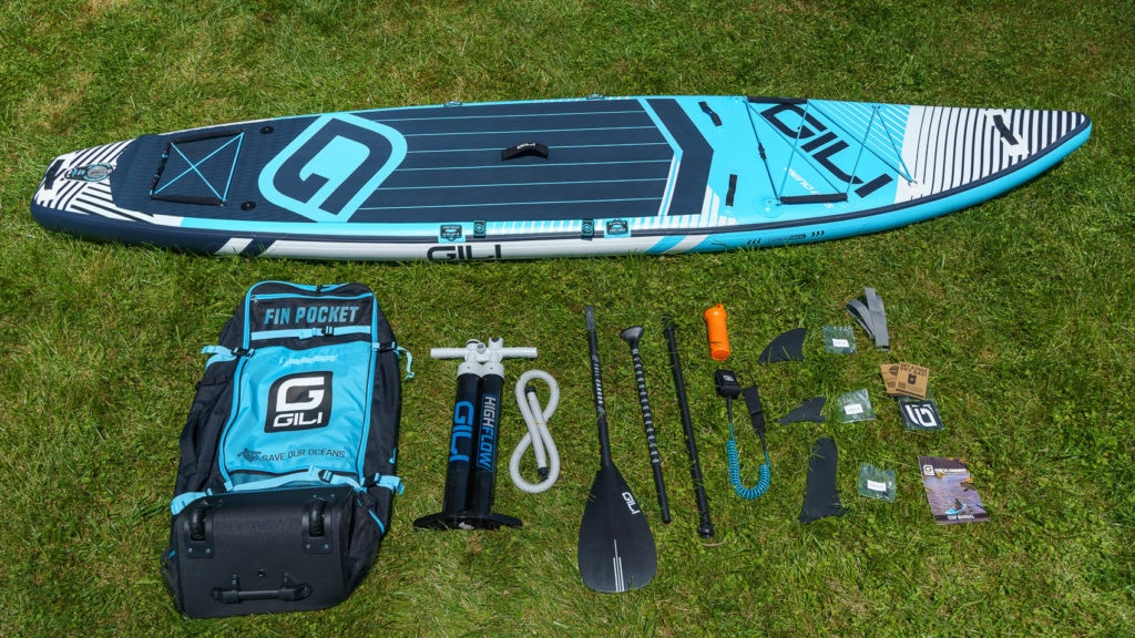 Unboxing the blue GILI Meno 12'6, featuring premium cag, dual chamber pump, carbon fiber paddle, SUP leash, 3 fins, repair kit, compression strap, and document package.