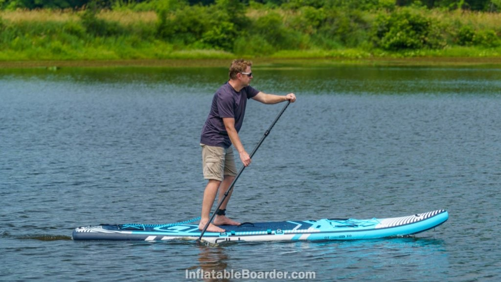 Side view of paddling the Meno on a lake.