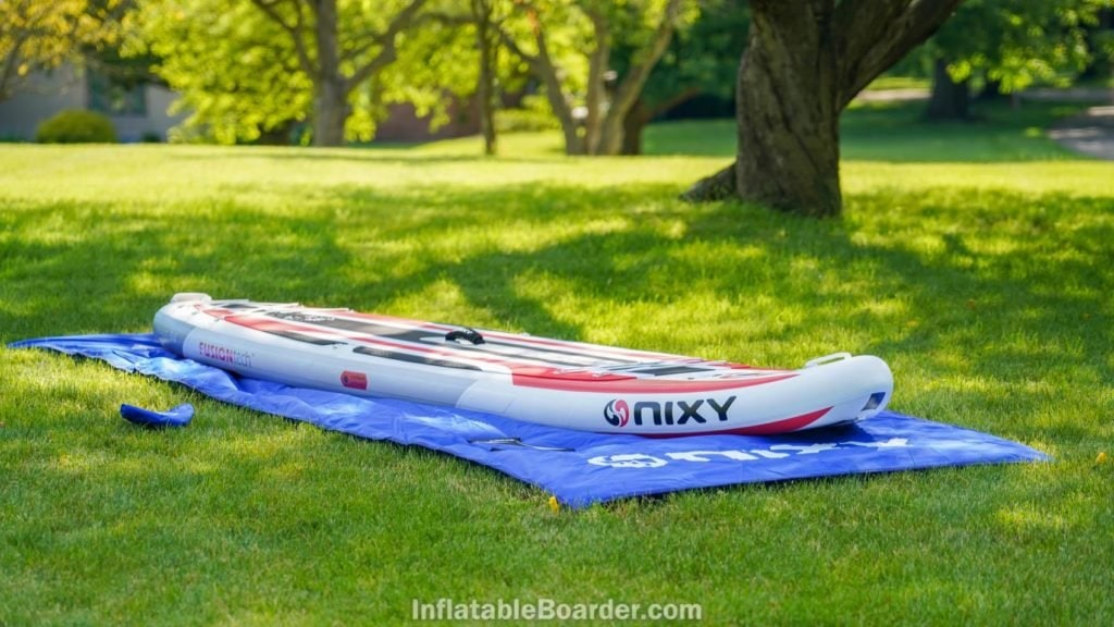 NIXY SUP landing mat rolled out with board and fins.