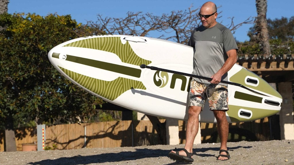 Carrying the Monterey SUP on a beach.