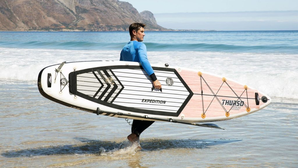 Thurso Expedition SUP being carried to ocean by a man.